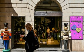 """A woman walks past a kid's luxury fashion clothing shop, on which a placard reads """"Close Out Sale, up 70 percent discount"""" on May 21, 2020 in Rome as the country eases its lockdown aimed at curbing the spread of the COVID-19 infection, caused by the novel coronavirus. - Many Italian shopkeepers, most of them restaurant owners, prefer not to reopen their business despite calls from the government to do so. (Photo by Vincenzo PINTO / AFP) (Photo by VINCENZO PINTO/AFP via Getty Images)"""