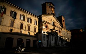 """A man rides his bicycle past Duomo of Santa Maria Assunta in Reggio Emilia, on May 15, 2019 Northern Italy. - The Unione Campanari Reggiani (Reggiani Ringers Bell Association) is a group of people that continues the secular tradition of ringers bell started in the Roman times. The school teach to young students how to use the modern technique to ring the bells in the tower of the Duomo of Reggio Emilia. The """"modern style"""" developed in the XVIII, consist to move tons of bronze bells with 4 or 6 people using hemp ropes. (Photo by MARCO BERTORELLO / AFP)        (Photo credit should read MARCO BERTORELLO/AFP via Getty Images)"""