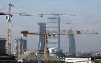 Alcune gru in azione e sullo sfondo i tre grattacieli di CityLife  a Milano ripresi dalla terrazza del Duomo il giorno dopo il blocco del traffico deciso per contrastare l'eccesso d'inquinamento nell'aria. Milano 3 Febbraio 2020.ANSA / MATTEO BAZZI