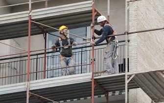 Due operai sui ponteggi di un palazzo in ristrutturazione, 18 aprile 2017 a Genova. ANSA/LUCA ZENNARO