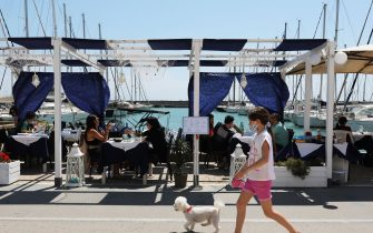 ROME, ITALY - MAY 24: A woman takes her dog for a walk while customers sit in a restaurant at the tourist harbor of Ostia have their lunch on May 24, 2020 in Rome, Italy. Romans were able to enjoy Ostia beach on the first weekend after the lockdown ended. Until May 29 it is permitted to practice sports, fish, walk and swim on the beach, but not stop or sunbathe. Nevertheless many people have not respected the prohibitions and some have been sanctioned by the numerous police forces in charge of the checks. (Photo by Marco Di Lauro/Getty Images)