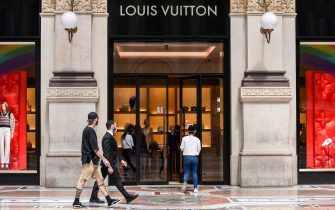 People enter and walk past a Louis Vuitton luxury fashion shop on May 18, 2020 in Milan's Vittorio Emanuele II shopping mall during the country's lockdown aimed at curbing the spread of the COVID-19 infection, caused by the novel coronavirus. - Restaurants and churches reopen in Italy on May 18, 2020 as part of a fresh wave of lockdown easing in Europe and the country's latest step in a cautious, gradual return to normality, allowing businesses and churches to reopen after a two-month lockdown. (Photo by Miguel MEDINA / AFP) (Photo by MIGUEL MEDINA/AFP via Getty Images)