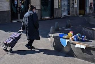 Una donna passeggia con una borsa per la spesa in una strada cittadina