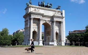 Una signora col cane all'Arco della Pace l'ultimo giorno della Fase 1 dell'emergenza Coronavirus a Milano, 3 maggio 2020.ANSA/Mourad Balti Touati