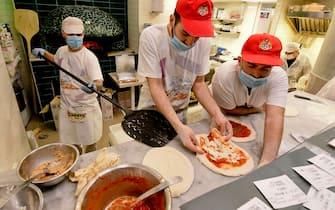 Super lavoro in una delle pizzerie aperte a Napoli dopo la chiusura imposta da coronavirus. Secondo  Antonio Pace, presidente dell'associazione Verace Pizza Napoletana, sono circa sessantamila quelle sfornate stasera in citta' , 27 aprile 2020  ANSA /CIRO FUSCO