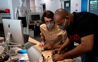 "A photo taken on May 21, 2020 shows engineers, wearing a face mask, working on prototypes of a smart device called ""iFeel-You"", a bracelet used to maintain safe distance between people in daily life situations as well as on the beach, at the Italian Institute of Technology ((IIT)) in Genoa, Liguria, as the country eases its lockdown during the Phase 2 of deconfinment within the COVID-19 infection, caused by the novel coronavirus. - ITT is aiming to find a company able to produce the bracelet on an industrial scale at low price in a short time. (Photo by MARCO BERTORELLO / AFP) (Photo by MARCO BERTORELLO/AFP via Getty Images)"