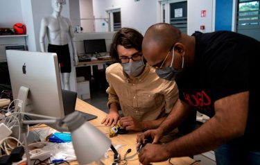 """A photo taken on May 21, 2020 shows engineers, wearing a face mask, working on prototypes of a smart device called """"iFeel-You"""", a bracelet used to maintain safe distance between people in daily life situations as well as on the beach, at the Italian Institute of Technology ((IIT)) in Genoa, Liguria, as the country eases its lockdown during the Phase 2 of deconfinment within the COVID-19 infection, caused by the novel coronavirus. - ITT is aiming to find a company able to produce the bracelet on an industrial scale at low price in a short time. (Photo by MARCO BERTORELLO / AFP) (Photo by MARCO BERTORELLO/AFP via Getty Images)"""