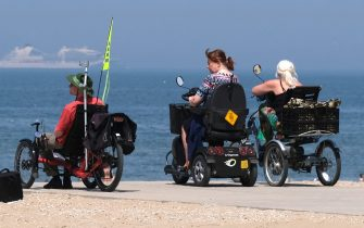 THE HAGUE, NETHERLANDS - MAY 21: People on motorized wheelchairs visit the Scheveningen beach on May 21, 2020 in The Hague, Netherlands. Dutch Prime Minister Mark Rutte said in a news conference on May 19, that restaurants, cafes, cinemas and museums can reopen with restrictions from June 1, as signs of the coronavirus (COVID-19) outbreak is coming under control.  (Photo by Yuriko Nakao/Getty Images)