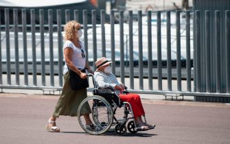 A woman pushes another one in a wheelchair in Barcelona's harbour, on July 18, 2020. - Four million residents of Barcelona have been urged to stay at home as virus cases rise, while EU leaders were set to meet again in Brussels, seeking to rescue Europe's economy from the ravages of the pandemic. (Photo by Josep LAGO / AFP) (Photo by JOSEP LAGO/AFP via Getty Images)