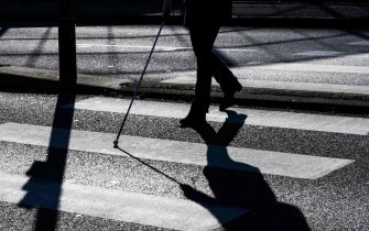 A blind person crosses a pedestrian crossing, on January 22, 2019 in Dardilly, central-eastern France. (Photo by JEFF PACHOUD / AFP)        (Photo credit should read JEFF PACHOUD/AFP via Getty Images)
