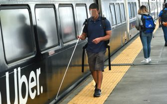 DENVER, COLORADO - AUGUST 30, 2019: A young blind man prepares to board a Denver RTD Light Rail train at Union Station in Denver, Colorado. (Photo by Robert Alexander/Getty Images)