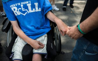 NEW YORK, NY - JULY 12: A father holds his son's hand during  the first annual Disability Pride Parade on July 12, 2015 in New York City. The parade calls attention to the rights of people with disabilities and coincides with the 25th anniversary of the Americans with Disabilities Act. (Photo by Stephanie Keith/Getty Images)