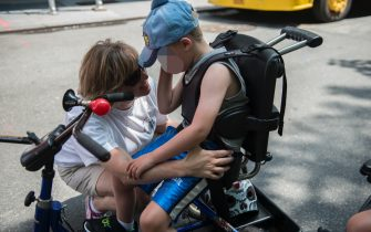 NEW YORK, NY - JULY 12: A mother comforts her son during the first annual Disability Pride Parade on July 12, 2015 in New York City. The parade calls attention to the rights of people with disabilities and coincides with the 25th anniversary of the Americans with Disabilities Act. (Photo by Stephanie Keith/Getty Images)