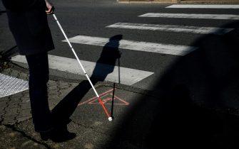 A blind person waits to cross a pedestrian crossing, on January 22, 2019 in Dardilly, central-eastern France. (Photo by JEFF PACHOUD / AFP)        (Photo credit should read JEFF PACHOUD/AFP via Getty Images)