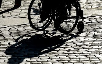 """A wheelchair-bound person casts a shadow as it is silhouetted during a 'Disability Pride Parade' by Italian disability organisations, on July 14, 2019 in central Rome. - July is designated as """"Disability Pride Month"""" in honor of the 29th anniversary of the Americans with Disabilities Act that aims to guarantee equal opportunities and rights for people with disabilities. (Photo by Andreas SOLARO / AFP)        (Photo credit should read ANDREAS SOLARO/AFP via Getty Images)"""