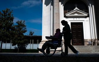 A nurse pushes an elderly resident in a wheelchair at the Tapparelli retirement home within visits of relatives on May 25, 2020 in Saluzzo near Cuneo, Piedmont, as the country eases lockdown measures taken to curb the spread of the COVID-19 pandemic, caused by the novel coronavirus. - the Tapparelli residence is home to 154 people, none of whom fell ill from the COVID-19. (Photo by MARCO BERTORELLO / AFP) (Photo by MARCO BERTORELLO/AFP via Getty Images)