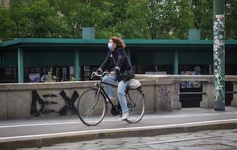 Un ciclita con il volto coperto da una mascherina percorre in bicicletta la pista ciclabile in viale Gorizia Darsena, 21 aprile 2020. Per favorire l'uso della bici in sicurezza, evitare l affollamento sui mezzi pubblici e disincentivare l'uso dell'autoil ilcomune di Milano stà considerando  l ampliamento della rete delle piste ciclabili a Milano in vista della fase di riapertura dopo il lockdown per  l emergenza epidemia coronavirus Covid-19. Milano 21 Aprile 2020. Ansa/Matteo Corner