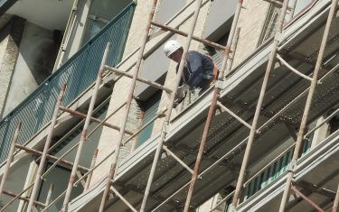 Un operaio edile sui ponteggi di un palazzo in ristrutturazione, 18 aprile 2017 a Genova. ANSA/LUCA ZENNARO