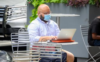 NEW YORK, NEW YORK - AUGUST 27: A person wears a protective face mask while using a laptop in an outdoor dining area in midtown as the city continues Phase 4 of re-opening following restrictions imposed to slow the spread of coronavirus on August 27, 2020 in New York City. The fourth phase allows outdoor arts and entertainment, sporting events without fans and media production. (Photo by Noam Galai/Getty Images)