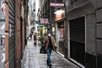 A resident wearing a protection mask carrying a shopping bag walks past typical food shops in the maze of alleys (Caruggi) of historic Genoa, Liguria, on March 13, 2020 as Italy shut all stores except for pharmacies and food shops in a desperate bid to halt the spread of a coronavirus. (Photo by Marco BERTORELLO / AFP) (Photo by MARCO BERTORELLO/AFP via Getty Images)