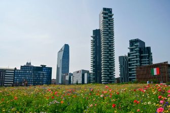 """A view from Milan's botanical park """"Library of Trees"""" in the Porta Nuova district on May 22, 2020 shows modern buildings and the Italian flag hanging from one of them (R), as the country eases its lockdown after over two months, aimed at curbing the spread of the COVID-19 infection, caused by the novel coronavirus. (Photo by MIGUEL MEDINA / AFP) (Photo by MIGUEL MEDINA/AFP via Getty Images)"""