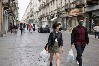 TURIN, ITALY - MAY 29: People wearing a protective mask walking through the streets of the city center on May 29, 2020 in Turin, Italy. The Piedmont Region in complete autonomy declared that from today 29 May it is mandatory to use the protective mask even outdoors to prevent further infections from Coronavirus (Covid 19). Many Italian businesses have been allowed to reopen, after more than two months of a nationwide lockdown meant to curb the spread of Covid-19. (Photo by Stefano Guidi/Getty Images)