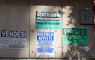 Alcuni cartelli di vendita e affitto immobili appesi ad un muro