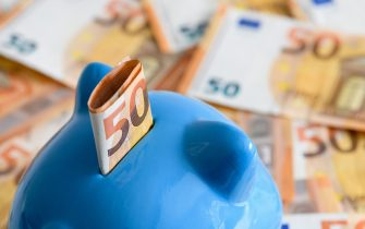 DORTMUND, GERMANY - APRIL 10: (BILD ZEITUNG OUT) In this photo illustration a blue piggy bank is seen in the bottom left corner with a 50 Euro bill. It looks at 50 Euro notes lying in the background on April 10, 2020 in Dortmund, Germany. (Photo by Alex Gottschalk/DeFodi Images via Getty Images)