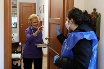 ROME, ITALY - MARCH 16: Giulia Baini, 24, a volunteer from the Community of Sant'Egidio, speaks to Giovanna, a frail elderly woman of 82 years of age during a home-care service on March 16, 2020 in Rome, Italy. The Italian Government has taken the unprecedented measure of a nationwide lockdown by closing all businesses except essential services such as, pharmacies, grocery stores, hardware stores, tobacconists and banks, in an effort to fight the world's second-most deadly Coronavirus (COVID-19) outbreak outside of China. Journeys are allowed only for work reasons and health reasons proven by a medical certificate. Citizens are encourage to stay home and have an obligation to respect a safety distance of one metre from each other in supermarkets or in public spaces. (Photo by Marco Di Lauro/Getty Images)