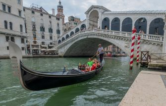 VENICE, ITALY - JULY 22: Gondolier takes tourists near the Rialto Bridge on July 22, 2020 in Venice, Italy. A new rule in Venice will make becoming a gondolier more difficult by asking to prove that you have been working for the last four years on a family Gondola. (Photo by Stefano Mazzola/Awakening/Getty Images)