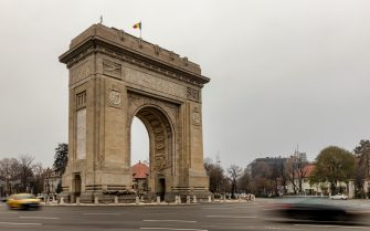 BUCHAREST, ROMANIA - DECEMBER 7: Vehicles pass by the Arcul de Triumf (The Arch Of Triumph) on December 7, 2018 in Bucharest, Romania. The Arch Of Triumph was built in 1922 to the memory of winning Word War I. (Photo by Laszlo Szirtesi/Getty Images)