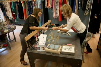 MIAMI, FL - JANUARY 30: Claudia Zamora (L) hands her credit card to Leslie Ames to ring up her purchase at Goldie  on January 30, 2014 in Miami, Florida. Data out from the Bureau of Economic Analysis showed that real gross domestic product grew at a rate of 3.2% in the fourth quarter 2013, which reflects growth in personal consumption expenditures among other things.   (Photo by Joe Raedle/Getty Images)