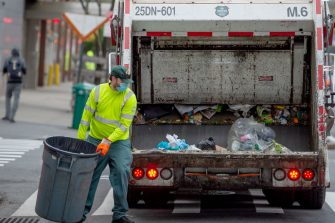 NEW YORK, NEW YORK - APRIL 30: A New York City Department of Sanitation worker wearing a mask and gloves collects the trash amid the coronavirus pandemic on April 30, 2020 in New York City, United States. COVID-19 has spread to most countries around the world, claiming over 230,000 lives with over 3.2 million cases. (Photo by Alexi Rosenfeld/Getty Images)