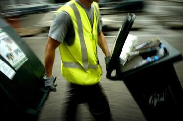 A dustman brings dumpsters to a waste truck, 06 July in Lyon, south France.  Un éboueur amène des bennes, le 06 juillet 2006 à Lyon, vers le camion de collecte des ordures.  AFP PHOTO JEFF PACHOUD (Photo by Jeff PACHOUD / AFP) (Photo by JEFF PACHOUD/AFP via Getty Images)