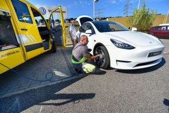 "A mechanic inflates a tyre of a ""Tesla Model Y"" car, an all-electric compact SUV by US electric car giant Tesla, on September 5, 2020 during its presentation at the Automobile Club in Budapest. (Photo by ATTILA KISBENEDEK / AFP) (Photo by ATTILA KISBENEDEK/AFP via Getty Images)"