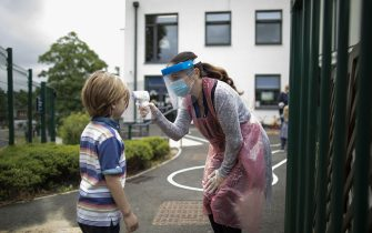 LONDON, ENGLAND - JUNE 04: A member of staff wearing personal protective equipment (PPE) takes a child's temperature at the Harris Academy's Shortland's school on June 04, 2020 in London, England. As part of Covid-19 lockdown measures, Harris Academy schools have taught smaller pods of students, to help maintain social distancing measures. With restrictions now lifting and the Government encouraging schools to re-open, the school staff has been working to find the best way to provide extra spaces while still retaining the correct social distancing measures and cleanliness requirements. This week, some schools across England reopened for some students, with children in reception, Year 1 and Year 6 allowed to return first. (Photo by Dan Kitwood/Getty Images)