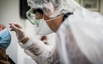 A medical assistant takes a sample from a patient for a coronavirus (Covid-19) test at an analysis laboratory in Le Peage-de-Roussillon, some 30kms south of Lyon, south-eastern France on September 22, 2020. (Photo by JEFF PACHOUD / AFP) (Photo by JEFF PACHOUD/AFP via Getty Images)