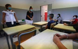 A teacher wearing a face mask (2ndL) addresses pupils, also wearing a face mask, on September 14, 2020 at the start of the school year at the Luigi Einaudi technical high school in Rome, during the the COVID-19 infection, caused by the novel coronavirus. - Schools in some European nations were set to open on September 14, 2020 with millions returning to classrooms in Italy, Greece and Romania. (Photo by Vincenzo PINTO / AFP) (Photo by VINCENZO PINTO/AFP via Getty Images)