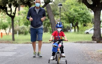 ROME, ITALY - MAY 12: The nephew of the photographer wears a face mask as he rides his bike along with his grandfather on May 12, 2020 in Rome, Italy. Italy was the first country to impose a nationwide lockdown to stem the transmission of the Coronavirus (Covid-19). (Photo by Elisabetta A. Villa/Getty Images)