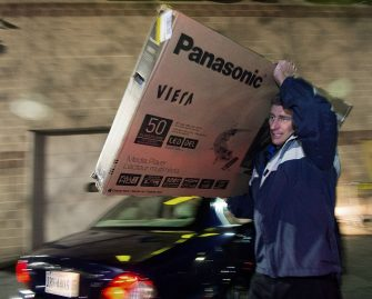 "A Best Buy employee carries a 50"" screen TV to car after being purchased during  the Black Friday doorbuster sale that started on Thursday November 27, 2014 at 5:00pm in Fairfax, Virginia.   Black Friday is a day of deep commercial discounts and frenzied shopping which takes place each year after the Thursday Thanksgiving holiday in the United States.        AFP Photo/Paul J. Richards        (Photo credit should read PAUL J. RICHARDS/AFP via Getty Images)"