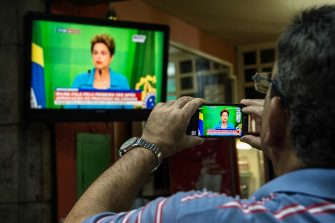 "TOPSHOT - A man records with his cell phone the speech of Brazilian President Dilma Roussef on tv,  in Rio de Janeiro, Brazil on April 18, 2016, Brazil. President Dilma Rousseff said Monday that she is ""outraged"" by a vote in Congress to authorize impeachment proceedings against her and vowed to keep fighting. / AFP / CHRISTOPHE SIMON        (Photo credit should read CHRISTOPHE SIMON/AFP via Getty Images)"