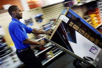 FORT LAUDERDALE, FL - JUNE 05:  James Belin, a Best Buy store customer specialist, wheels a digital ready flat screen television set to a checkout counter on June 5, 2009 in Fort Lauderdale, Florida. On June 12, America switches to the digital television signal making old analog televisions obsolete unless a converter box has been purchased. For the last 70 plus years people have watched television on analog. (Photo by Joe Raedle/Getty Images)