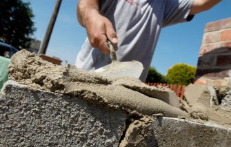 Man preparing mortar for bricklaying, close up. (Photo by BuildPix/Construction Photography/Avalon/Getty Images)