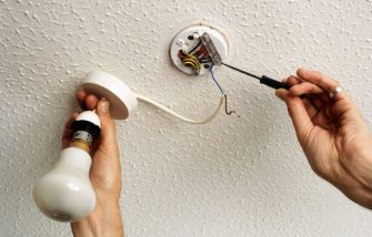 Wiring a lamp on a ceiling. (Photo by DIY Photolibrary/Construction Photography/Avalon/Getty Images)