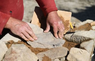 French self-taught artisan Olivier Thomas places a stone to restore a wall in front of the Locmaria manor house in Carnoet, western France, on August 22, 2019. - Olivier Thomas has taught himself the arts and crafts of a mason, a carpenter and an artist blacksmith to restore the manor of Locmaria, a 14th century house in Carnoet, in central Brittany. (Photo by Fred TANNEAU / AFP)        (Photo credit should read FRED TANNEAU/AFP via Getty Images)