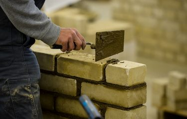 COLOGNE, GERMANY - NOVEMBER 24:  Students with an immigrant background working as a bricklayer at the Vocational training center of the Chamber of Crafts (Bildungszentrum Butzweilerhof der Handwerkskammer) on November 24, 2015 in Cologne, Germany. German industry has complained in recent years of being unable to fill tens of thousands of trainee positions and some see the influx of nearly a million migrants this year as a possible opportunity to narrow the gap.  (Photo by Sascha Schuermann/Getty Images)