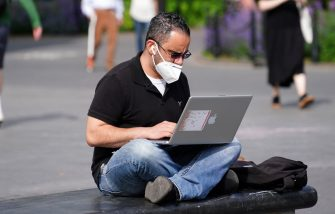NEW YORK, NEW YORK - MAY 27: A man wearing a protective mask uses a laptop in Washington Square Park during the coronavirus pandemic on May 27, 2020 in New York City. Government guidelines encourage wearing a mask in public with strong social distancing in effect as all 50 states in the USA have begun a gradual process to slowly reopen after weeks of stay-at-home measures to slow the spread of COVID-19. (Photo by Cindy Ord/Getty Images)