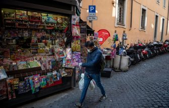 ROME, ITALY - MARCH 12: A man wearing a protective mask walks near an open newsstand during the Coronavirus emergency, on March 12, 2020, in Rome, Italy. The Italian Government has taken the unprecedented measure of a nationwide lockdown by closing all businesses except essential services such as, pharmacies, grocery stores, hardware stores and tobacconists and banks, in an effort to fight the world's second-most deadly coronavirus (COVID-19) outbreak outside of China. The movements in and out are allowed only for work and health reasons proven by a medical certificate. The number of confirmed cases of the Coronavirus COVID-19 disease in Italy has jumped up to at least 10590 while the death toll has surpassed 827. (Photo by Antonio Masiello/Getty Images)