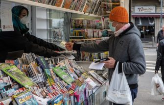 MILAN, ITALY - MARCH 11: A newsagent handles some newspapers to a customer at a news kiosk on March 11, 2020 in Milan, Italy. The Italian Government has strengthened up its quarantine rules, shutting all commercial activities except for pharmacies, food shops, gas stations, tobacco stores and news kiosks in a bid to stop the spread of the novel coronavirus. (Photo by Emanuele Cremaschi/Getty Images)