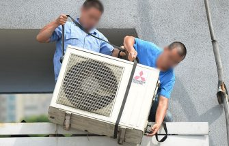 Workers install an airconditioning unit in a food stall in Shanghai on July 2, 2013. The Shanghai Meteorological Bureau forecast a heat wave as temperatures reached 38 degrees celcius in the city according to state run media. AFP PHOTO / Peter PARKS        (Photo credit should read PETER PARKS/AFP via Getty Images)